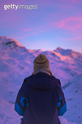 Rear View Of Woman Wearing Warm Clothing While Looking At Snowcapped Mountain During Sunset - gettyimageskorea
