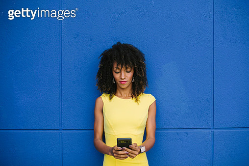 Portrait of fashionable businesswoman in yellow dress text messaging against blue background - gettyimageskorea