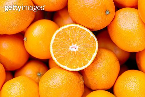 Half of orange on the heap of oranges - gettyimageskorea