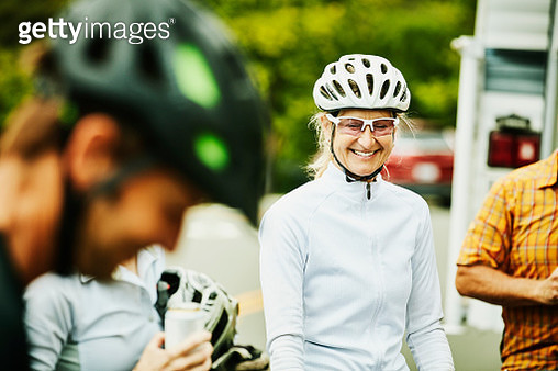 Smiling mature woman relaxing with friends after bike ride - gettyimageskorea