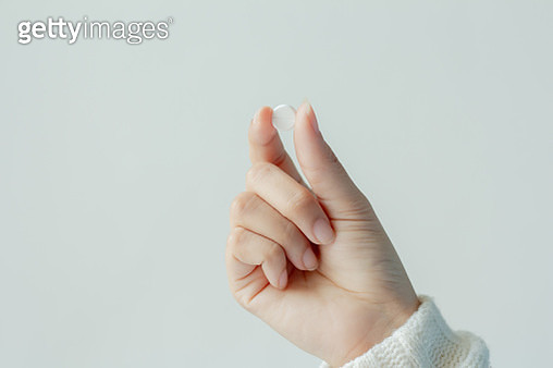 Close-Up Of Hand Holding Pill Against White Background - gettyimageskorea