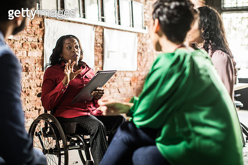 Businesswoman in wheelchair leading group discussion in creative office - gettyimageskorea