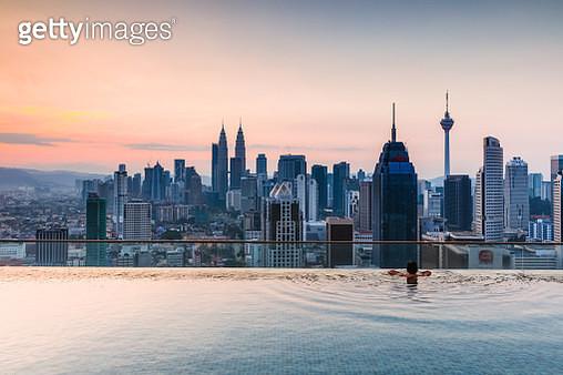 Man in a infinity pool with Kuala Lumpur skyline, Malaysia - gettyimageskorea