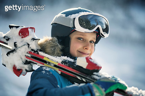 Little boy carrying skis on a winter day - gettyimageskorea