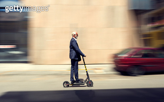 Senior businessman cruising on a scooter through city - gettyimageskorea