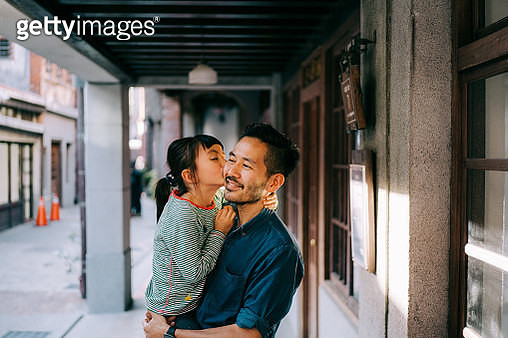 Young Eurasian girl kissing her Japanese father on street in Taiwan - gettyimageskorea