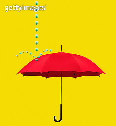 Stream of blue balls falling on red umbrella on yellow background - gettyimageskorea