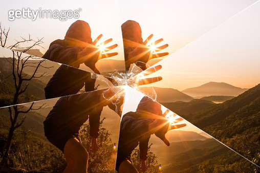 Mystic picture of guy playing with sunlight during sunrise in the nature seen through a broken mirror. - gettyimageskorea