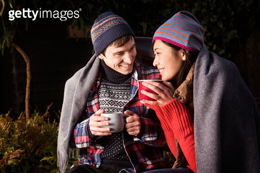 Couple with warm drink,under blanket outdoors. - gettyimageskorea