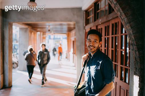 Japanese man smiling at camera on street - gettyimageskorea