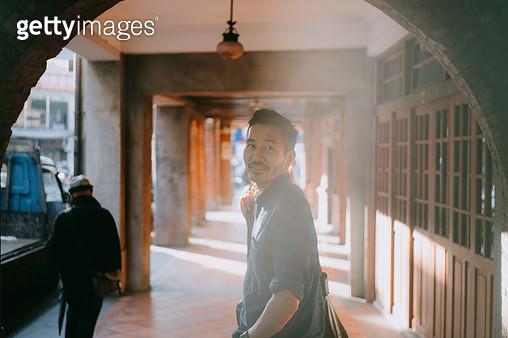 Japanese man walking and smiling at camera on street - gettyimageskorea