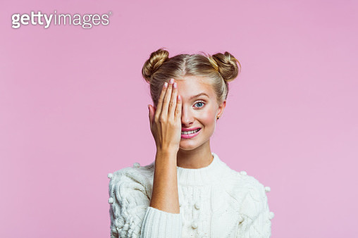 Portrait of happy teenager wearing white sweater. Girl covering her eye with hand and smiling at camera. Studio shot on pink background. - gettyimageskorea