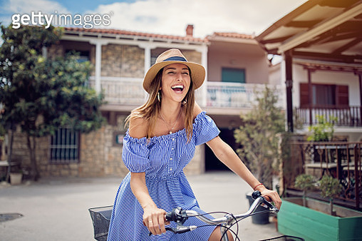 Young beautiful woman is riding bicycle in small sea town - gettyimageskorea