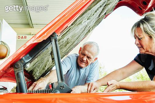 Mature woman and senior man repairing a car, looking under bonnet. - gettyimageskorea