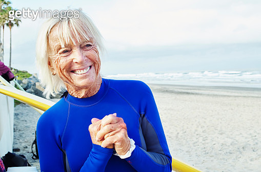 Smiling senior woman wearing a wetsuit, standing on a sandy beach. - gettyimageskorea