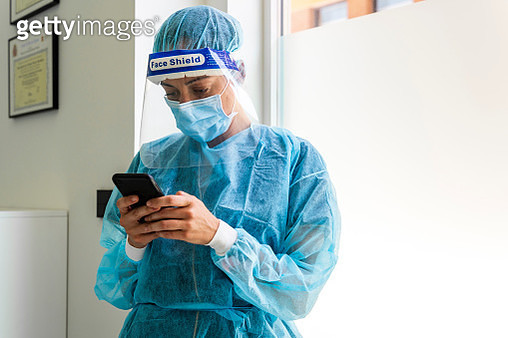 Female dentist texting through smart phone in clinic - gettyimageskorea