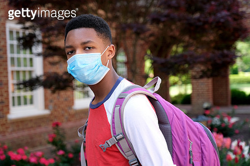 African American teenager wearing backpack and facial mask to protect himself from Coronavirus. - gettyimageskorea