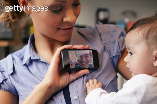 Baby girl watching father on video call, mother holding smartphone - gettyimageskorea