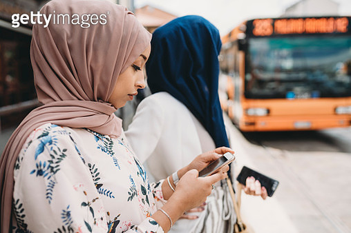 Friends waiting for the bus at the bus stop in the city - gettyimageskorea