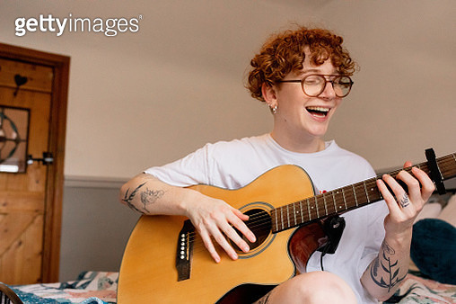 A portrait of a young LGBT person at home playing guitar - gettyimageskorea