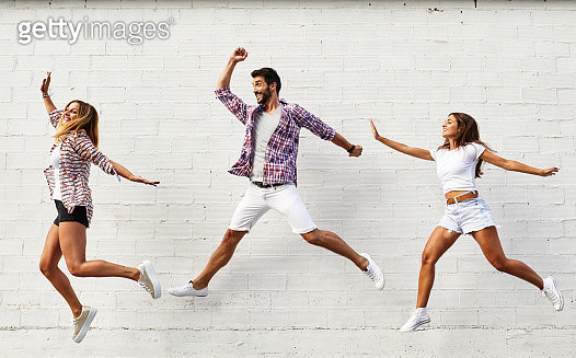 Three friends jumping mid-air in front of white wall - gettyimageskorea