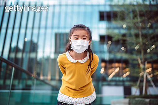 Lovely little girl in medical face mask leaning forward to the camera while smiling joyfully in front of an office building - gettyimageskorea