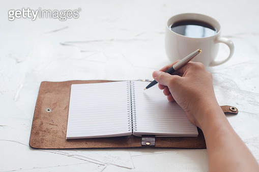 A young man is writing a journal on a white wooden table with coffee cup - gettyimageskorea