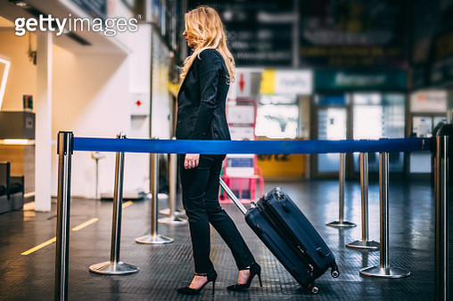 Businesswoman pulling suitcase towards airport check-in counter - gettyimageskorea