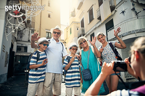 Multi generation family enjoying summer vacations. The family is walking in the narrow streets of Amalfi. Teenage girl is taking photo of posing family.Nikon D850 - gettyimageskorea