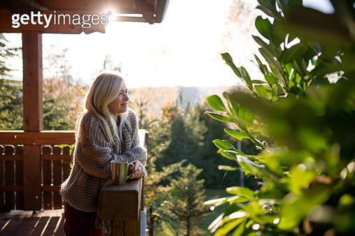 Happy senior woman with tea outdoors on terrace in autumn, relaxing. - gettyimageskorea