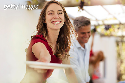 Smiling woman handing over plate on agarden party - gettyimageskorea