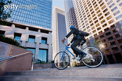 Businessman riding bicycle in city - gettyimageskorea
