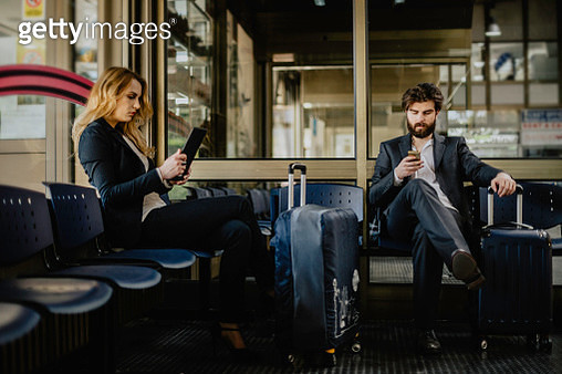 Two business people at the airport waiting for flight - gettyimageskorea