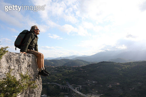 Male hiker relaxes on rock ledge above hills, contemplative - gettyimageskorea