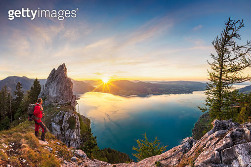 Mountain Climber at sunset with View To Lake Attersee from Schober- Sunset at Mount Schoberstein, Alps - gettyimageskorea