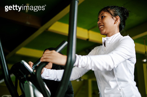 Beautiful Asian Woman Exercising Using Exercise Bike at The Gym - gettyimageskorea