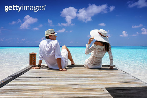 Rear View Of Sitting On Wooden Jetty At Beach Against Sky - gettyimageskorea