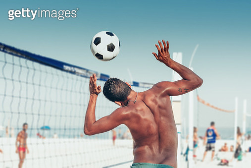 brazilian man heading soccerball over volleyball net at beach - gettyimageskorea