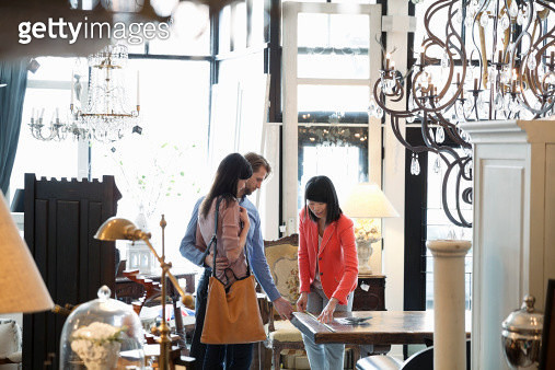Female business owner helping customers in furniture store - gettyimageskorea