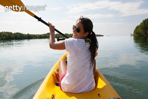 Hispanic woman paddling kayak - gettyimageskorea