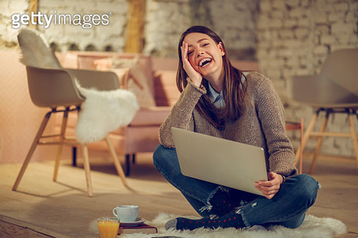 Young woman having video conference using laptop at home. - gettyimageskorea