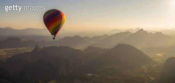 Hot Air Balloon Flying Over Mountains Against Sky - gettyimageskorea