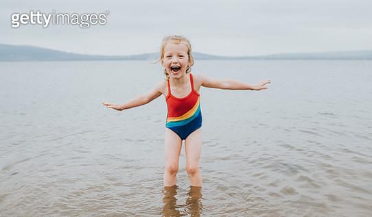 Joyful little girl Paddling in the Sea, wearing a Rainbow swimming costume - gettyimageskorea