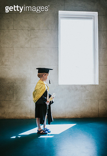 Young child wearing graduation gown and cap - gettyimageskorea