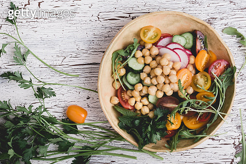 Veggie chickpeas salad with fresh vegetables, colorful mix cherry tomatoes, arugula, radishes, cucumbers on wooden table, healthy vegan bowl.  plant based meal, top view - gettyimageskorea