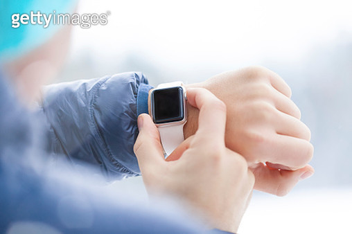 Sportive man checking his smartwatch in winter, close-up - gettyimageskorea