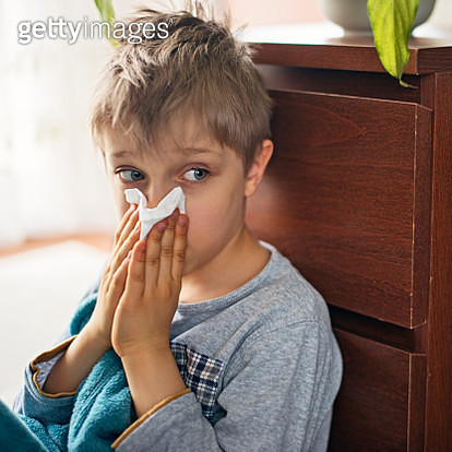 Cute sick little boy blowing nose at home - gettyimageskorea