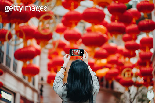 Rear view of woman taking photos of traditional Chinese red lanterns with smartphone on city street - gettyimageskorea