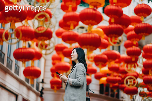 Smiling young woman using mobile phone in the city, with traditional Chinese red lanterns on the background - gettyimageskorea