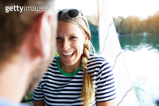 Young woman laughing at man at a lake next to sailing boat - gettyimageskorea